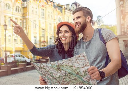 Young couple woman and man tourists city walk together vacation holding map
