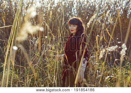 Beautiful young woman in long skirt and red wool scarf standing outdoors in high grass. Outdoor shot. Natural background. Fall.