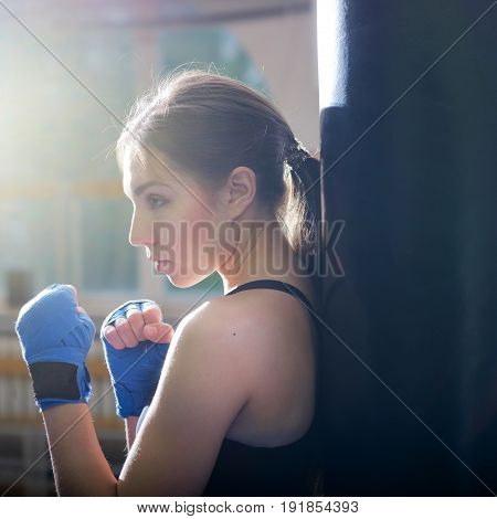 Young adult sexy boxing girl posing with gloves. Confident woman ready to fight. Side view