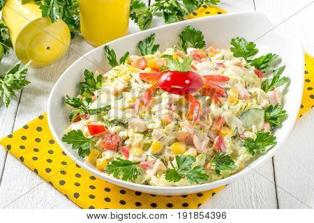 Fresh vegetable salad with chinese cabbage and surimi. Decorated with crab made from sweet pepper. Bowl with salad is on blue napkin containers for salt and pepper parsley on white wooden table