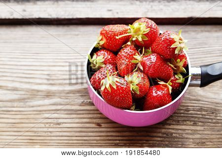 Fresh ripe red strawberries on wooden table in natural background