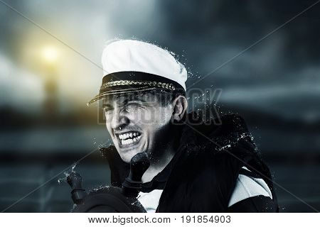 helmsman with vest and cap struggle against storm in front of blurred coast and light tower