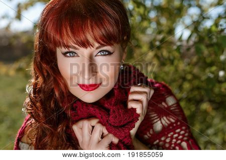 Beautiful young woman in long skirt and red wool scarf standing outdoors in countryside. Outdoor shot. Natural background. Copy space. Closeup portrait.