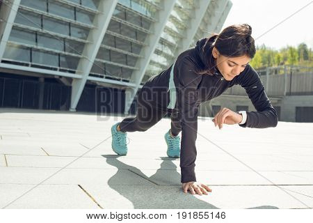 Young femaleactive exercise workout on street outside checking time