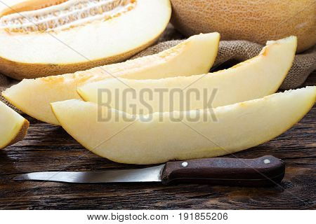 Juicy ripe melon cut into slices on a brown wooden table next to it is half a melon
