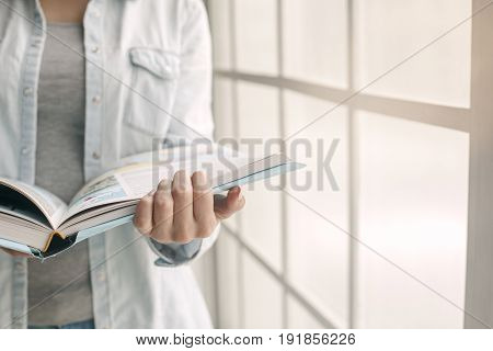 Young woman study at home alone reading a book