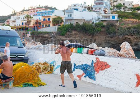 Bali Island Crete Greece - June 30 2016: Man is a fisherman carries a big fish (sawfish) after successful fish catch from the fishing boat.