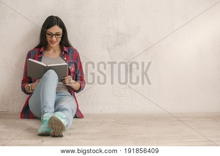 Young female with a book isolated on white reading
