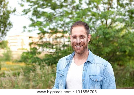 Portrait of a casual men with denim shirt in a park