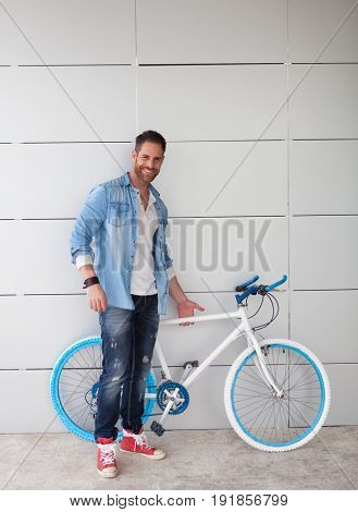 Casual guy with a vintage blue and white bike wearing denim shirt