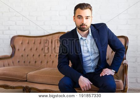Business, Richness And Success Concept - Handsome Man In Business Suit Sitting On Vintage Sofa