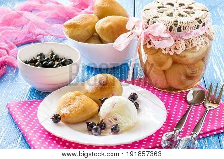 Small rich sponge cake baba typically soaked in rum-flavored syrup. Canned sponge cake rum baba in jar. Is related to brioche and savarin. Served with ice cream rum syrup and blackcurrant