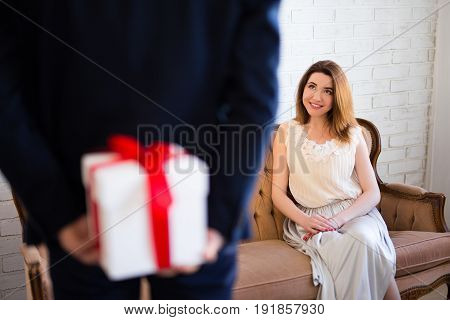 Valentine's Day Or Anniversary Concept - Man Hiding Gift Box From His Girlfriend