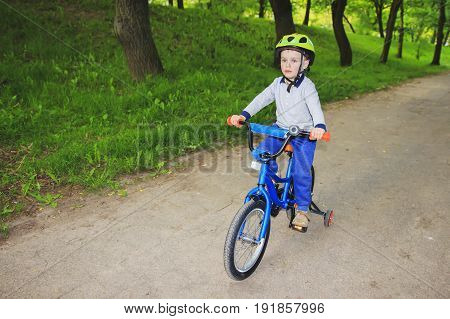 A little boy kid is riding a children's bicycle in a green park in the summer. The child on a vacation rides a bicycle