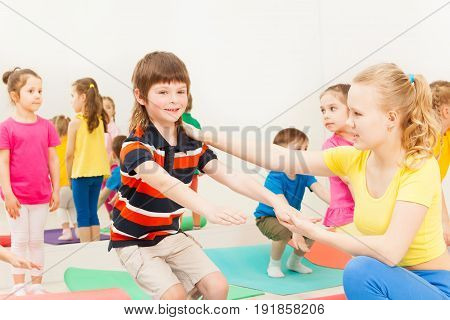 Portrait of female instructor teaching kid boy how to do squats correctly during gymnastics