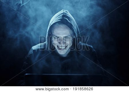 Programmer in a smoke-filled background, a hacker in a hood, a hacker on a dark background.