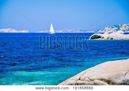 White sailboat, yacht between granite rocks in sea, amazing azure water, Sardinia, Italy.