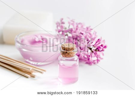 homemade organic soap, cream, extract in lilac cosmetic set with flowers on white table background