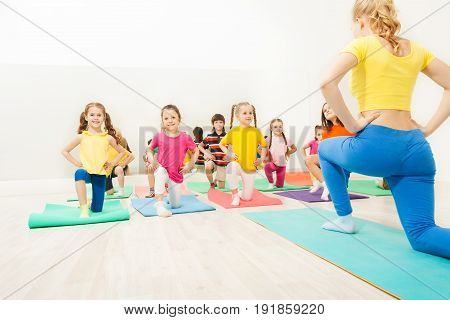 Group of happy kids doing exercises in gym with female gymnastics coach