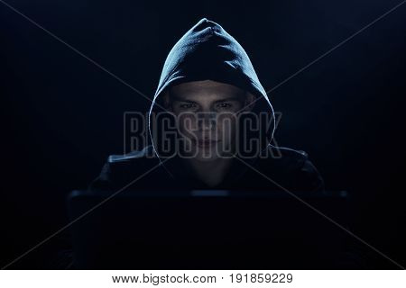 Hacker in the hood, the programmer hacks the network, the hacker on a dark background.