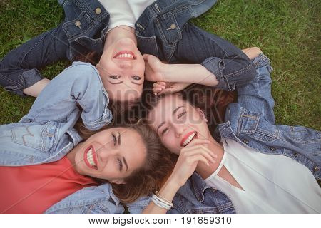 Happy friends in the park on a sunny day . Summer lifestyle portrait of three women enjoy nice day. Best friends girls having fun, joy.
