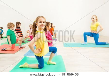 Side view portrait of smiling six years old girl, standing on knee holding hands on her waist, during gymnastic activity in gym with female coach