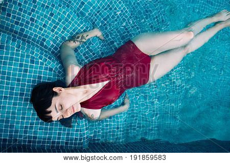 Attractive sexy woman lays in cyan turquoise swimming pool in one piece swim suit relaxed and chill taking rest from summer heat