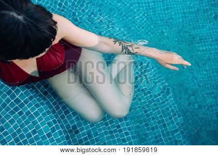 Millennial hipster female with authentic unconventional tattoos lays down inside blue pool to cool down from summer heat