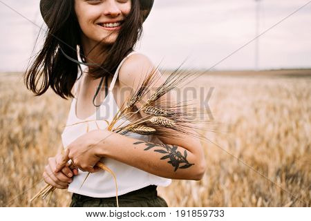 Femenine lady in thin silk white top and khaki panama hat and authentic hipster arm tattoos smiles to camera in middle of wheat field