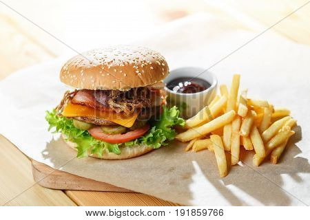 Big tasty burger and fries on the wooden table. fried bacon and onion rings. Lettuce and slices of tomato