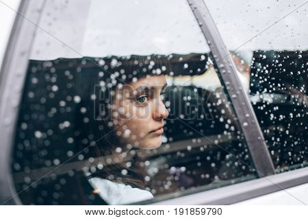 Close up of sad and offended girl sitting inside the car while it rains and storms outside she looks in hope her boyfriend will come to pick her up in taxi