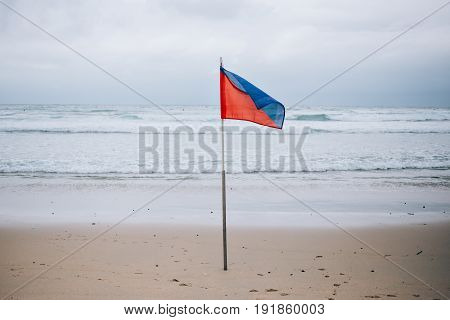 Photo of high hazard red and blue flag on stormy windy beach cautioning surfers and tourists not to enter ocean sea waters
