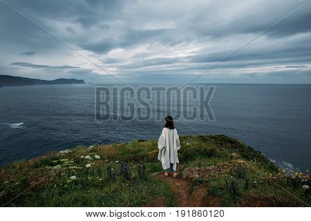 Young hipster nomad girl in casual clothing stands on edge of cliff contemplating and meditating finding peace and tranquility within herself