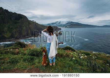 Young female traveler and adventurer overlooks amazing landscape together with her best friend and partner dog pet concept friendship tranquility