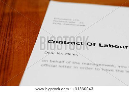 A letter on a wooden table - employment agreement
