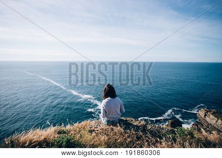 Young woman with dark hair sits on edge of cliff dreamingly overlooks ocean waves and horizon makes photo of herself and nature