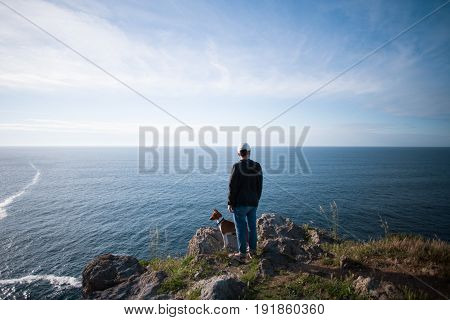 Tall young man in urban casual clothing stands on edge of mountain and overlooks ocean views on sunset together with best friend basenji little puppy