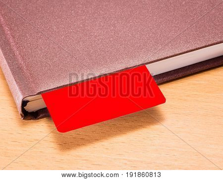 Business style diary with a red bookmark on a wooden background a place for writing and advertising