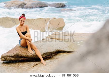 Beautiful Girl In Short Shorts Sit On Big Stones.
