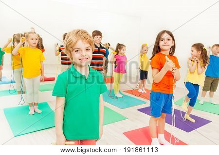 Portrait of happy kid boy playing jumping rope with friends in gym