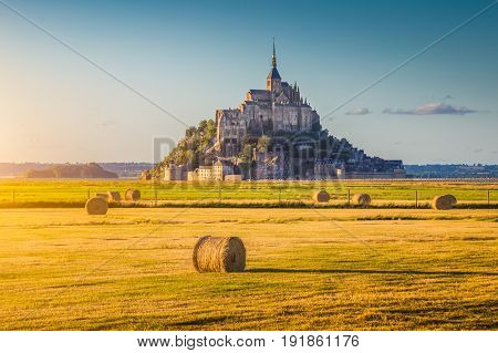 Beautiful view of famous historic Le Mont Saint-Michel in golden evening light at sunset in summer with hay bales on fields with retro vintage Instagram style pastel filter effect Normandy France