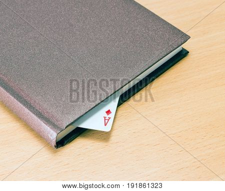 Ace of ace as a bookmark in a solid diary on a wooden background concept of success