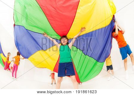 Fish eye picture of kid boy standing under big tent made of colorful parachute in gym
