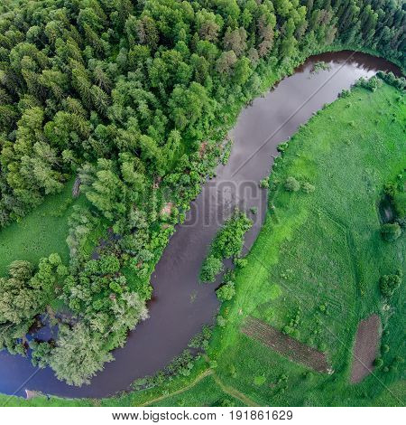Steep bend of the river. Forest and meadow on the banks. You can see a small island. A bird's-eye view. Sot River in the Yaroslavl Region. Russia.