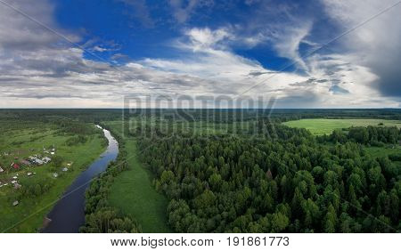 A small village on one side of the river and on the other side of the forest. Beautiful blue sky with white clouds. Evening. The Sot River. A bird's-eye view. Yaroslavl region. Russia