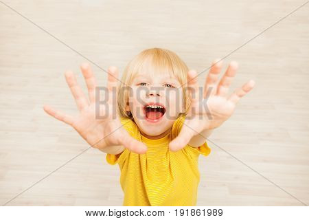 Top view portrait of joyful five years old boy lifting hands upward