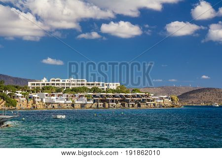 A large hotel by the sea. A boat is visible. Good weather. Day. Gulf of Mirabelo. Crete. Greece