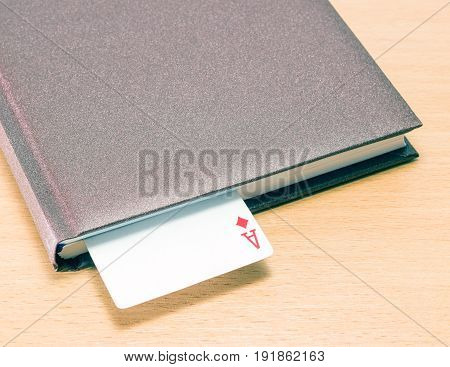 Ace of diamonds in a diary on a wooden background it symbolizes good luck in business