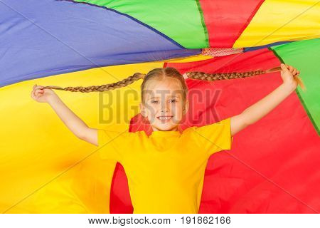Cute little girl with two braids standing under the tent made of colorful parachute