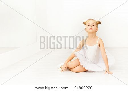Portrait of little dancer, beautiful six years old girl in white tutu, sitting on the floor of light ballet studio